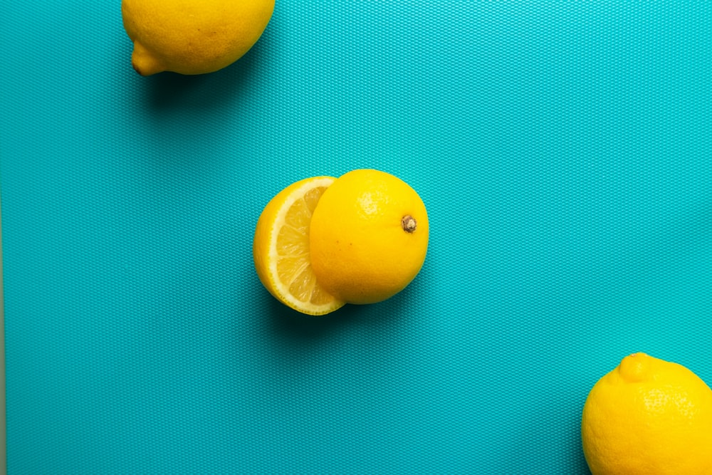 two yellow lemon fruits on blue surface
