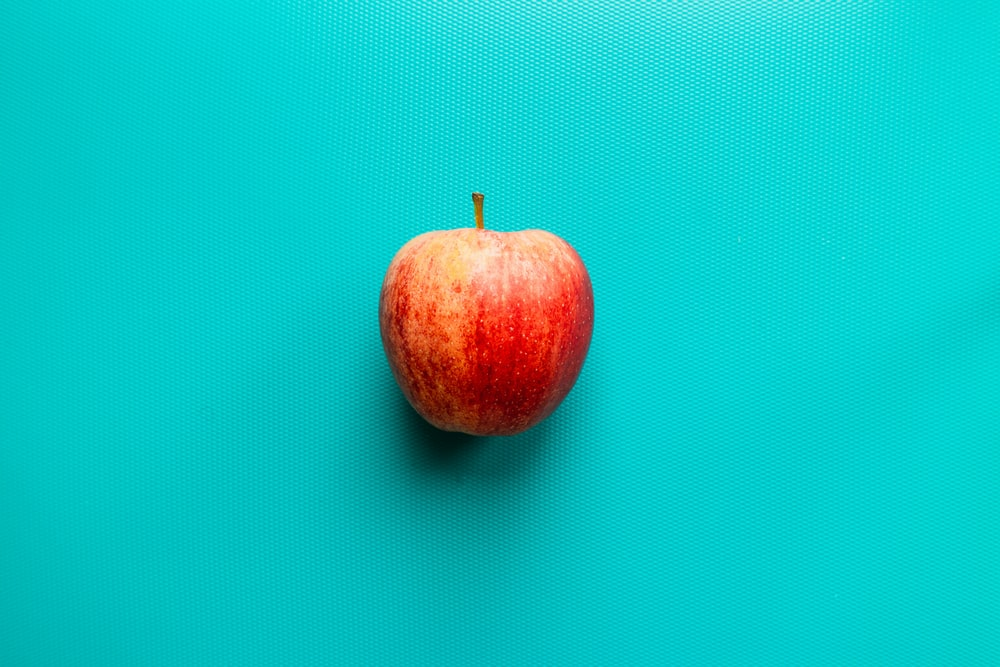 red apple fruit on blue surface