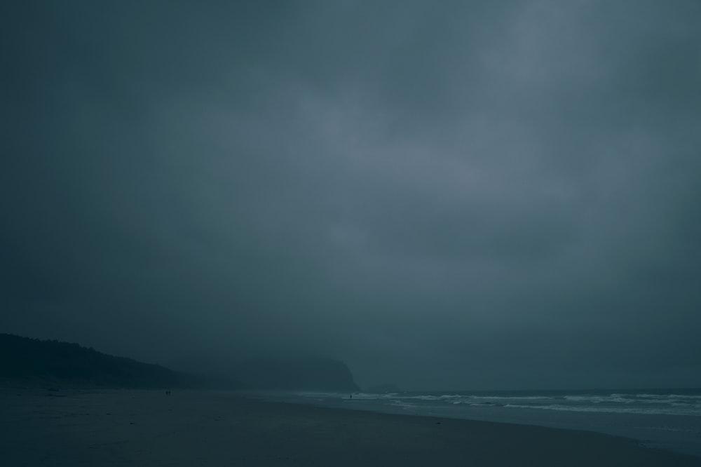 body of water near mountain under gray sky