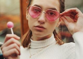 woman in white turtleneck sweater wearing red framed eyeglasses holding pink lollipop
