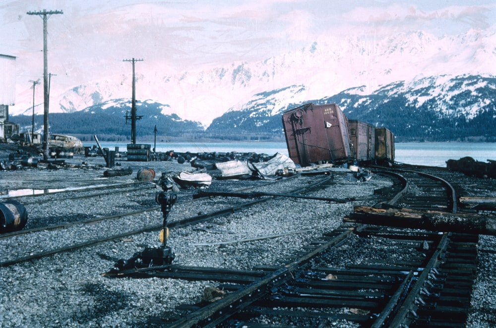 red and black train on rail tracks near snow covered mountain during daytime