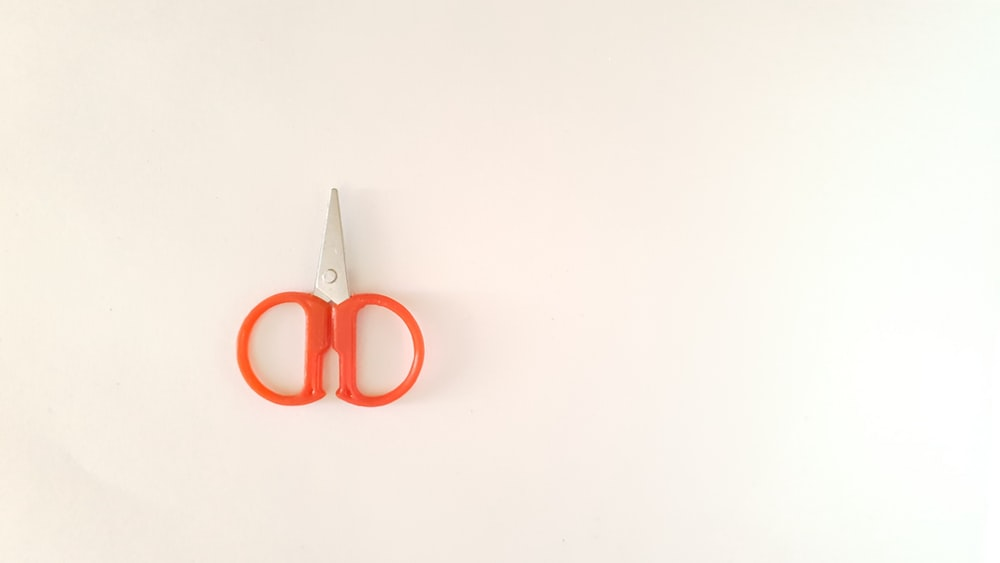 orange and silver scissors on white table