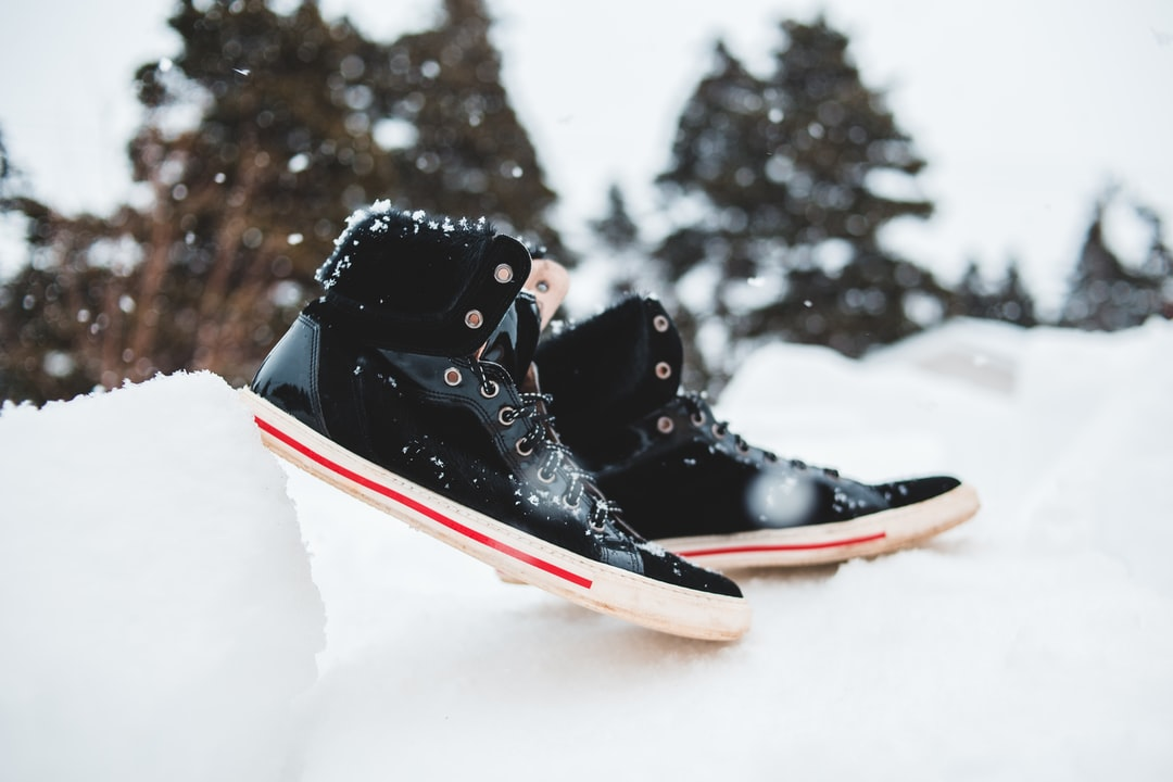 Black Red and White Air Jordan 1s On Snow Covered Ground - unsplash