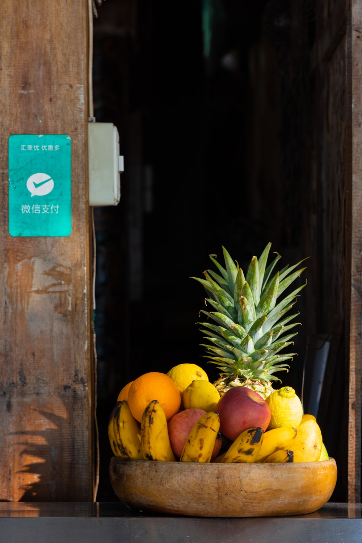 yellow banana fruit on brown wooden shelf