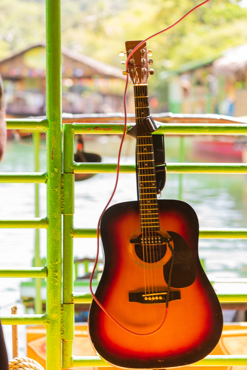 brown acoustic guitar on green metal fence