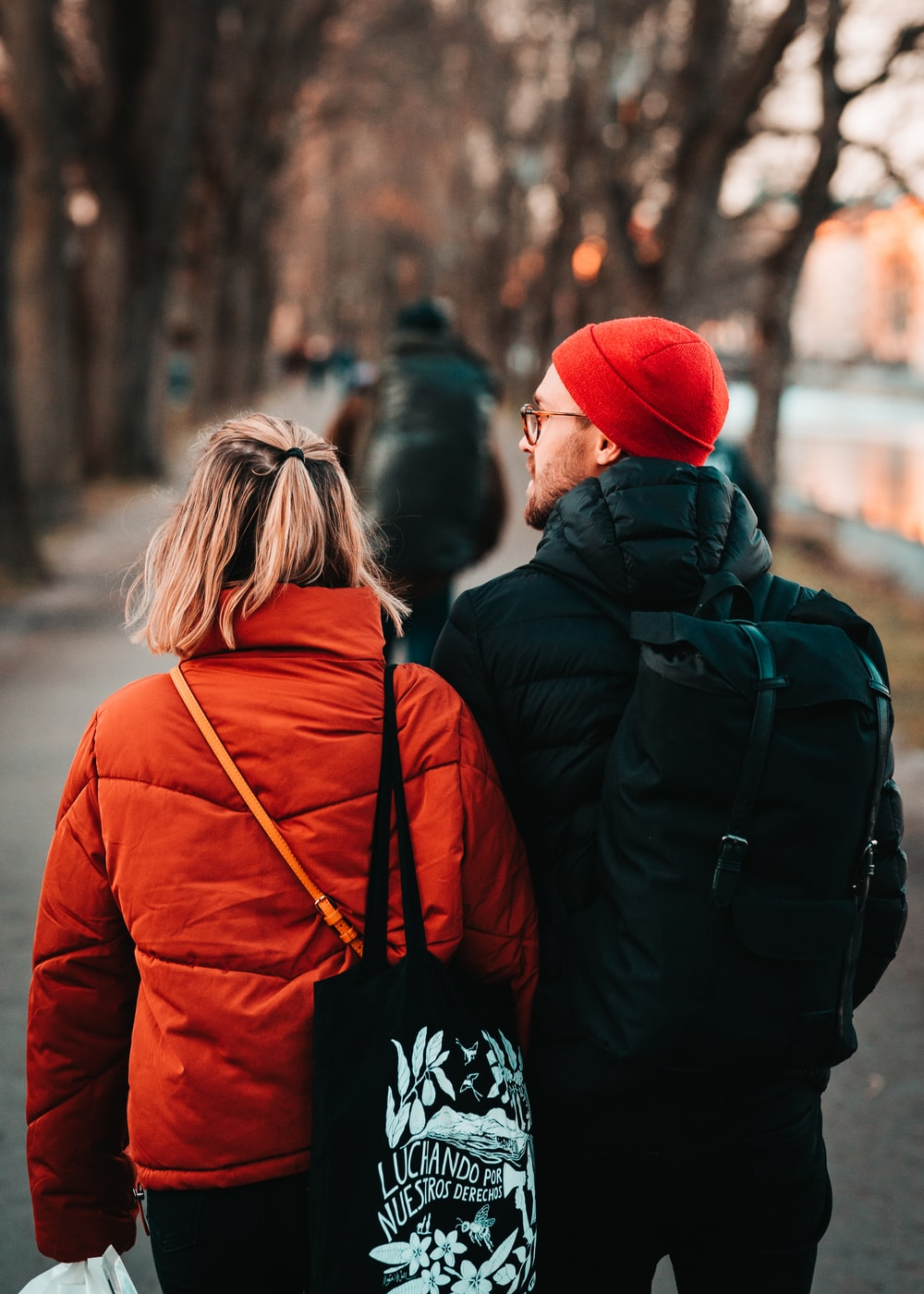 woman in red knit cap and red jacket standing in front of man in black jacket