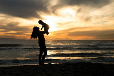 silhouette of man and woman kissing on beach during sunset mother teams background