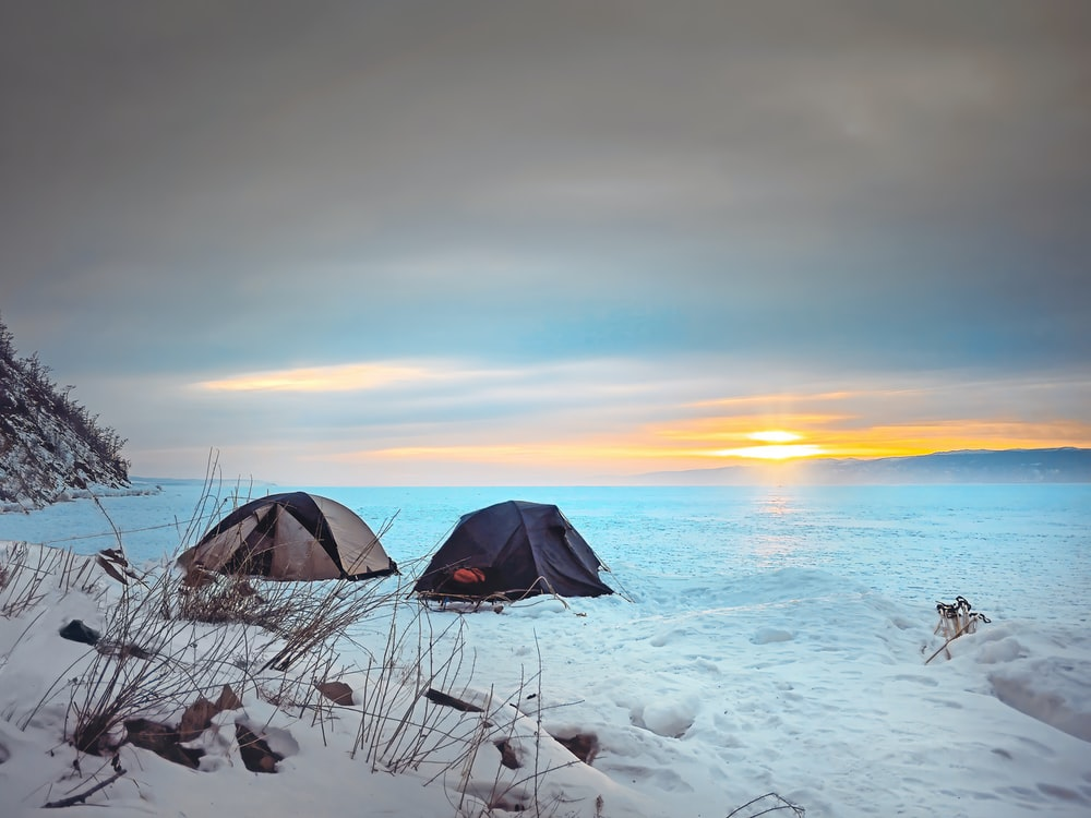 black tent on snow covered ground during sunset