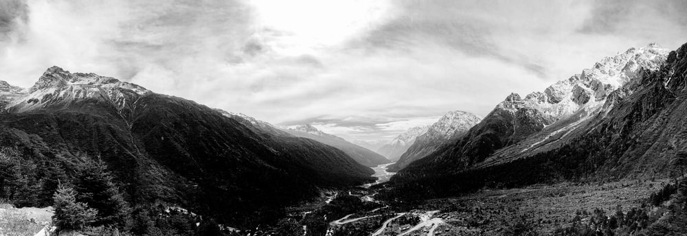 grayscale photo of mountains and river