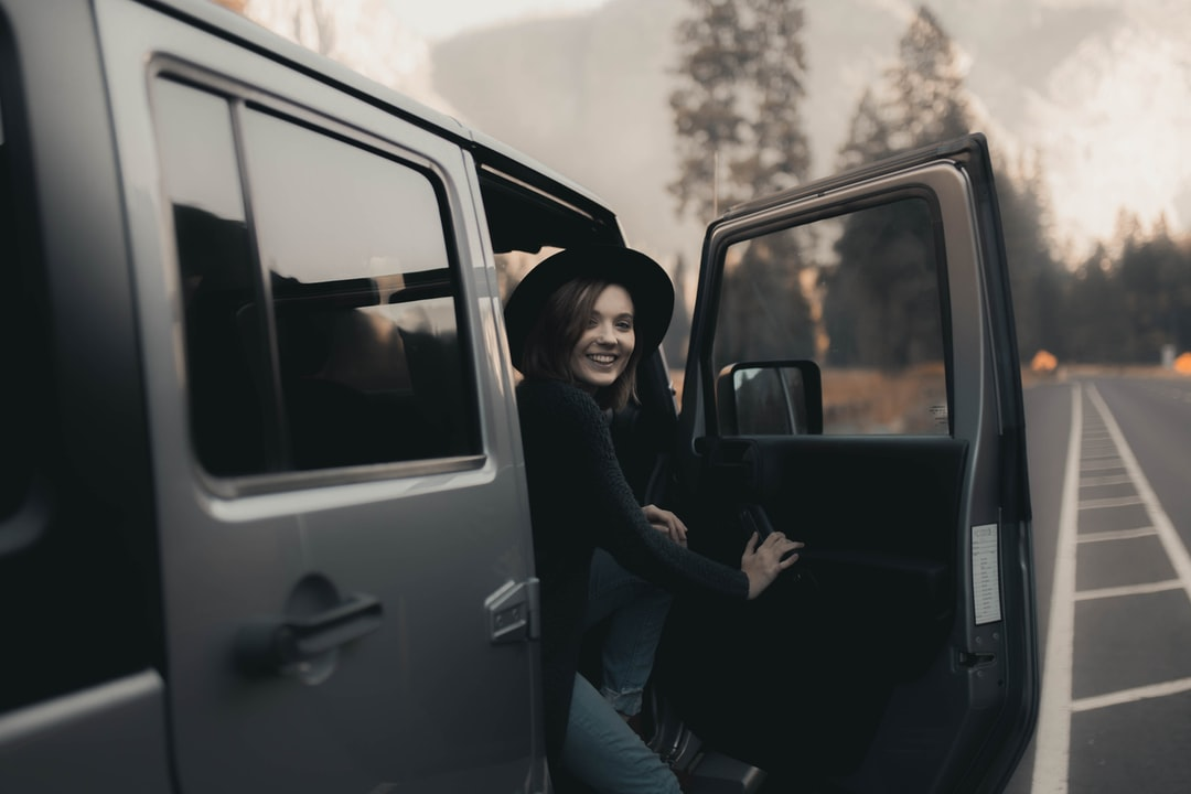 Woman In Black Long Sleeve Shirt Sitting On Car Seat - unsplash
