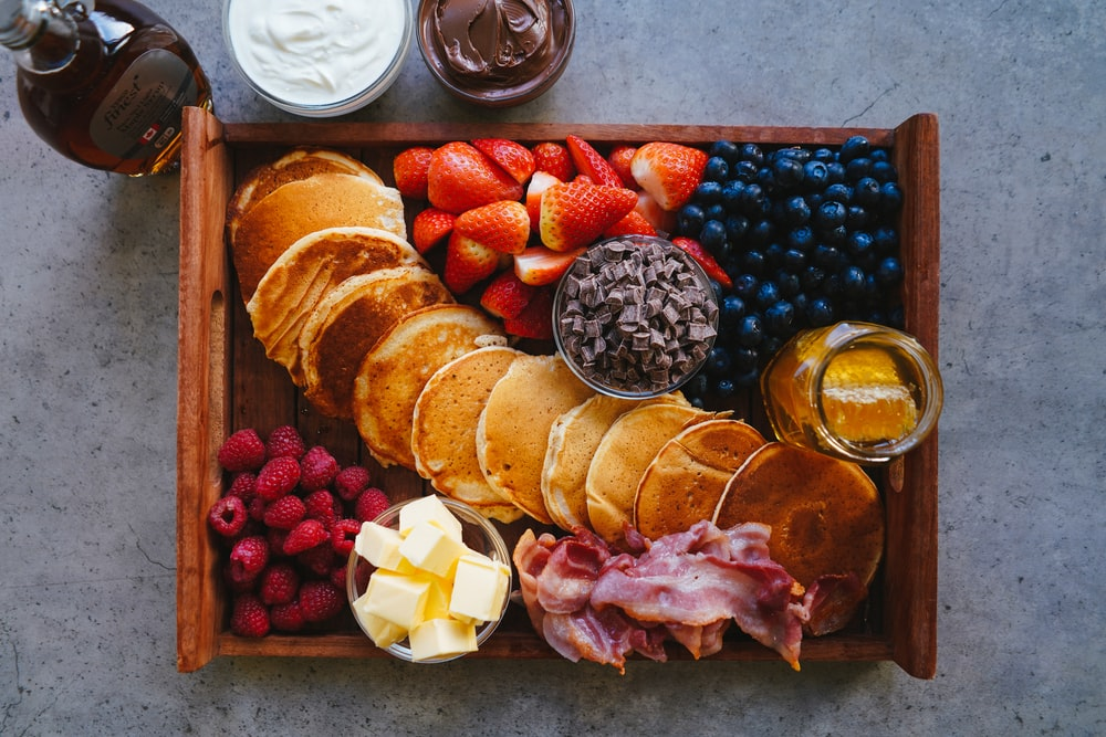 sliced bread and sliced fruits on brown wooden tray
