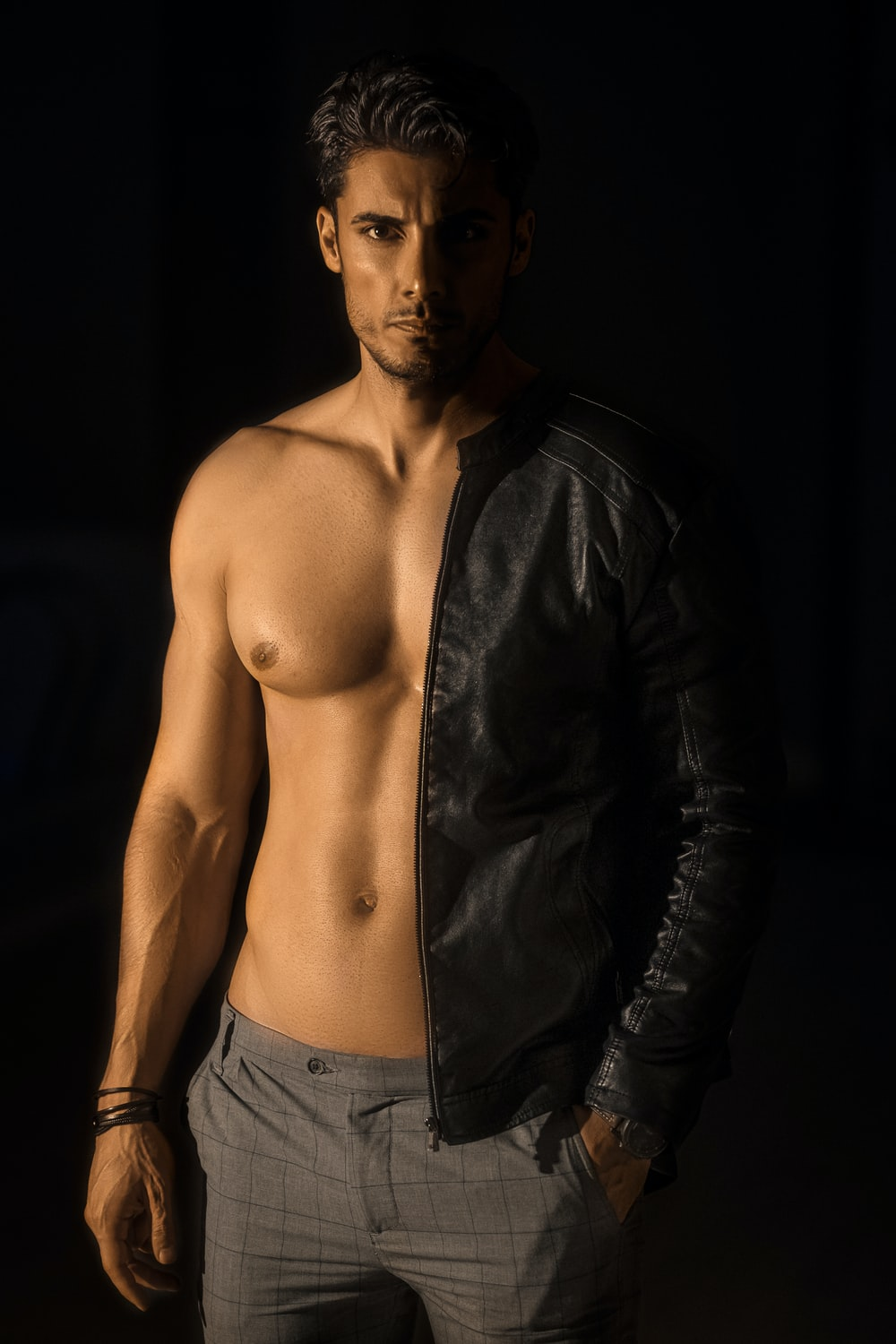 topless man in black leather jacket