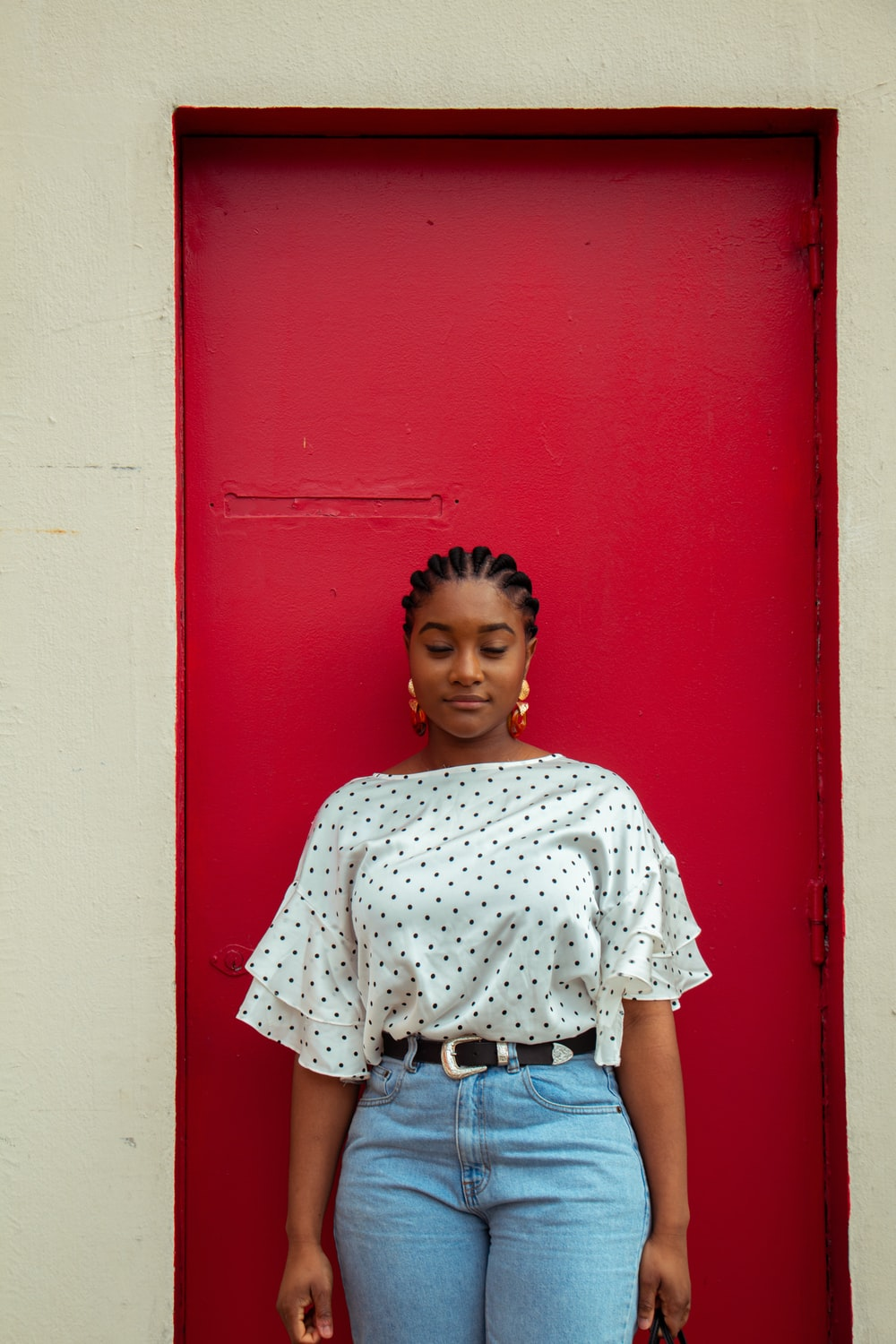 girl in white and red floral shirt standing beside red wall