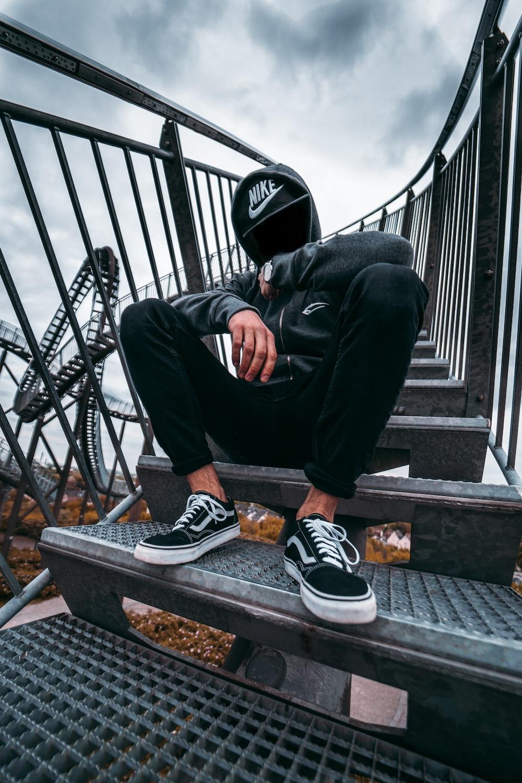 man in black pants and black and white nike sneakers sitting on black metal railings