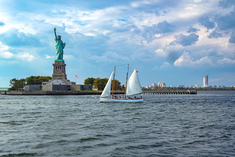 white sail boat on sea near statue of liberty under cloudy sky during daytime