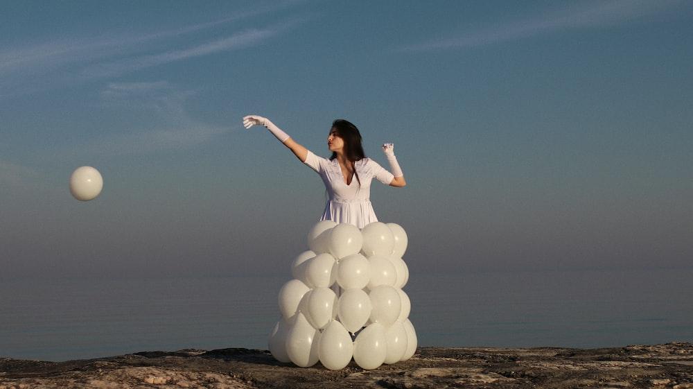 woman in white dress holding white balloons