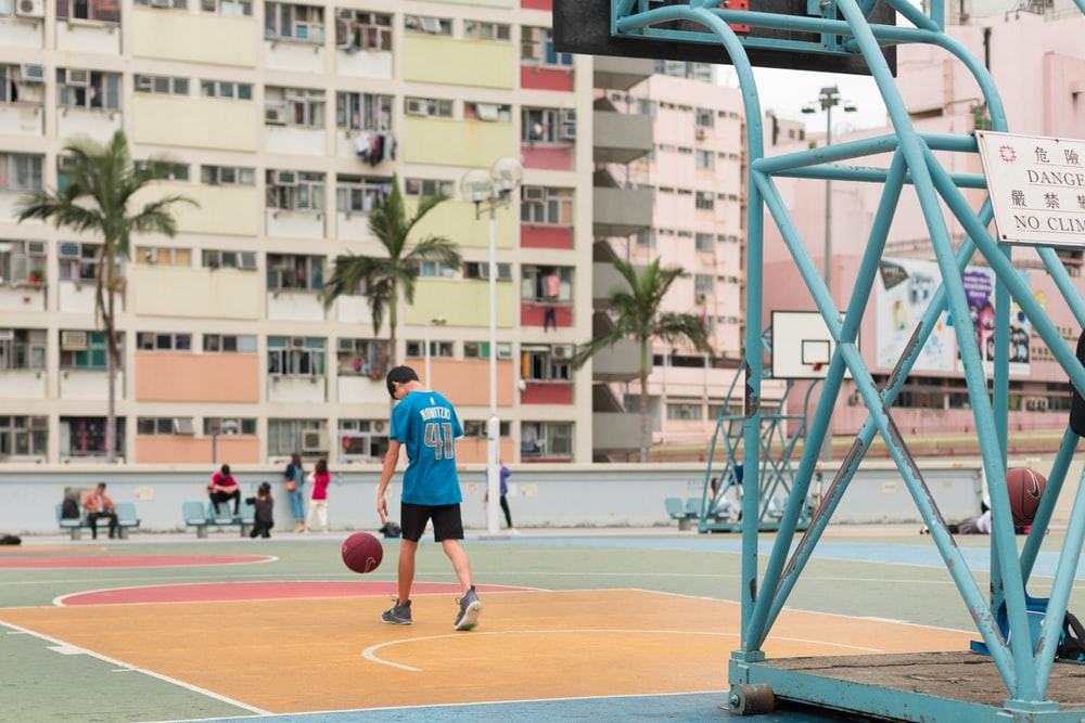 man in blue and red basketball jersey playing basketball