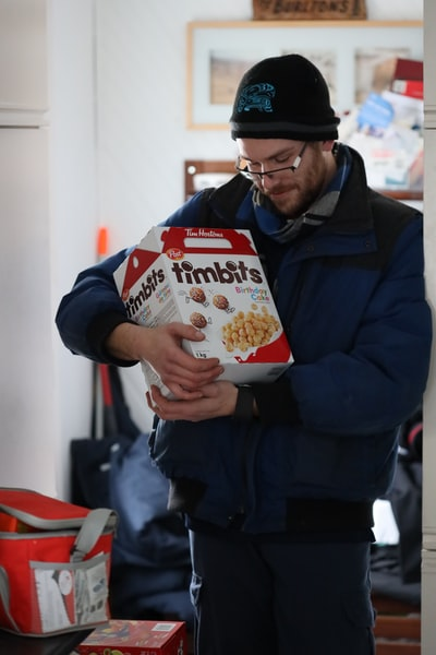 man in black jacket holding white and orange carton