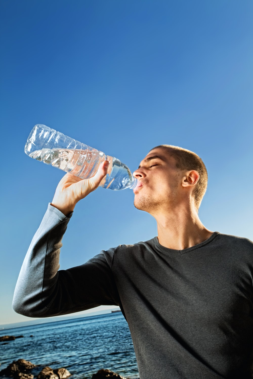 man in black crew neck shirt drinking water