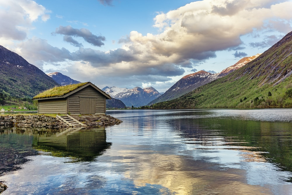 Places where Sun never sets -brown wooden house on lake near green mountains under white clouds and blue sky during daytime