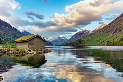 brown wooden house on lake near green mountains under white clouds and blue sky during daytime norway teams background
