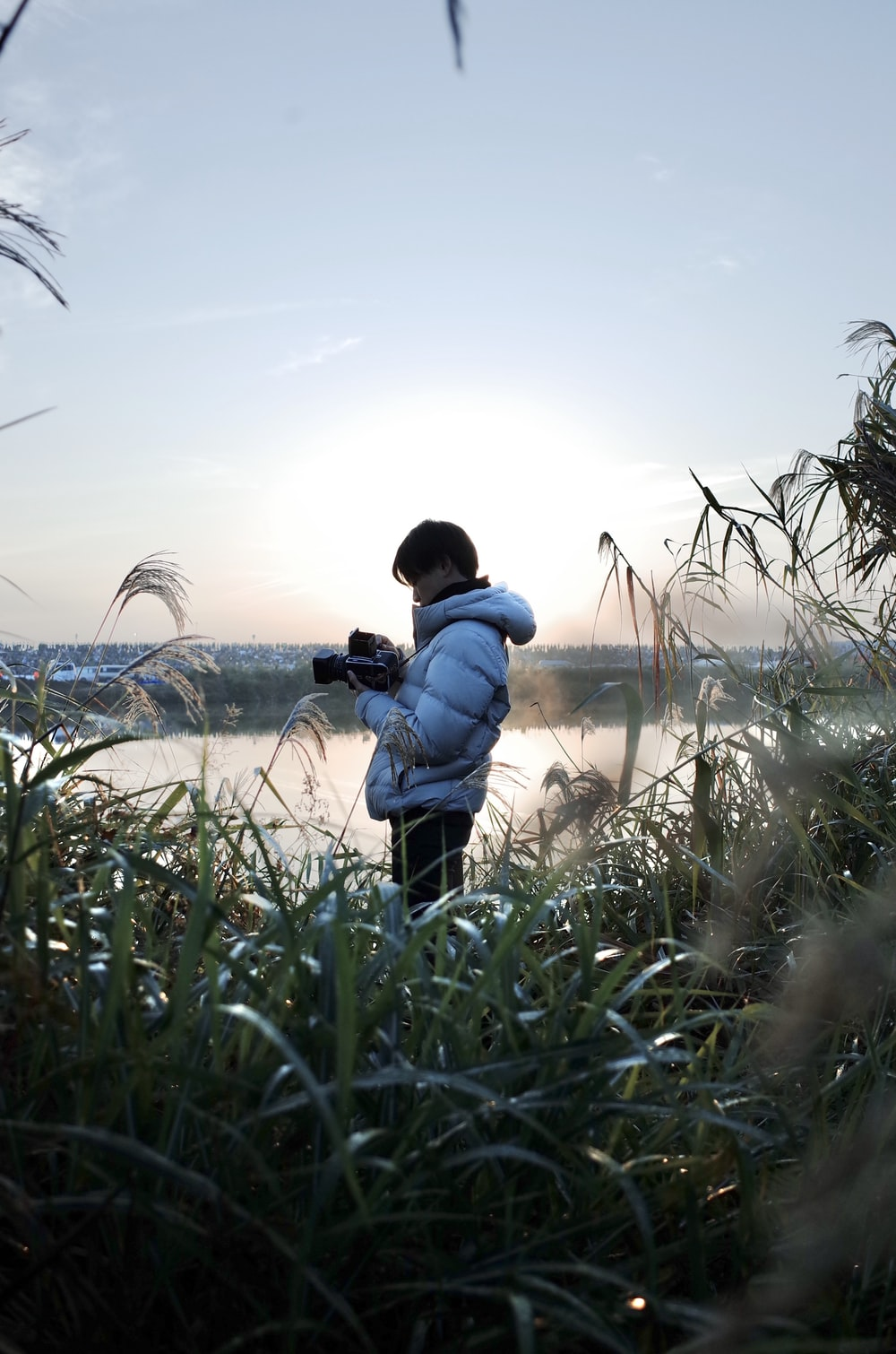 man in blue jacket and black pants holding black dslr camera standing on green grass field