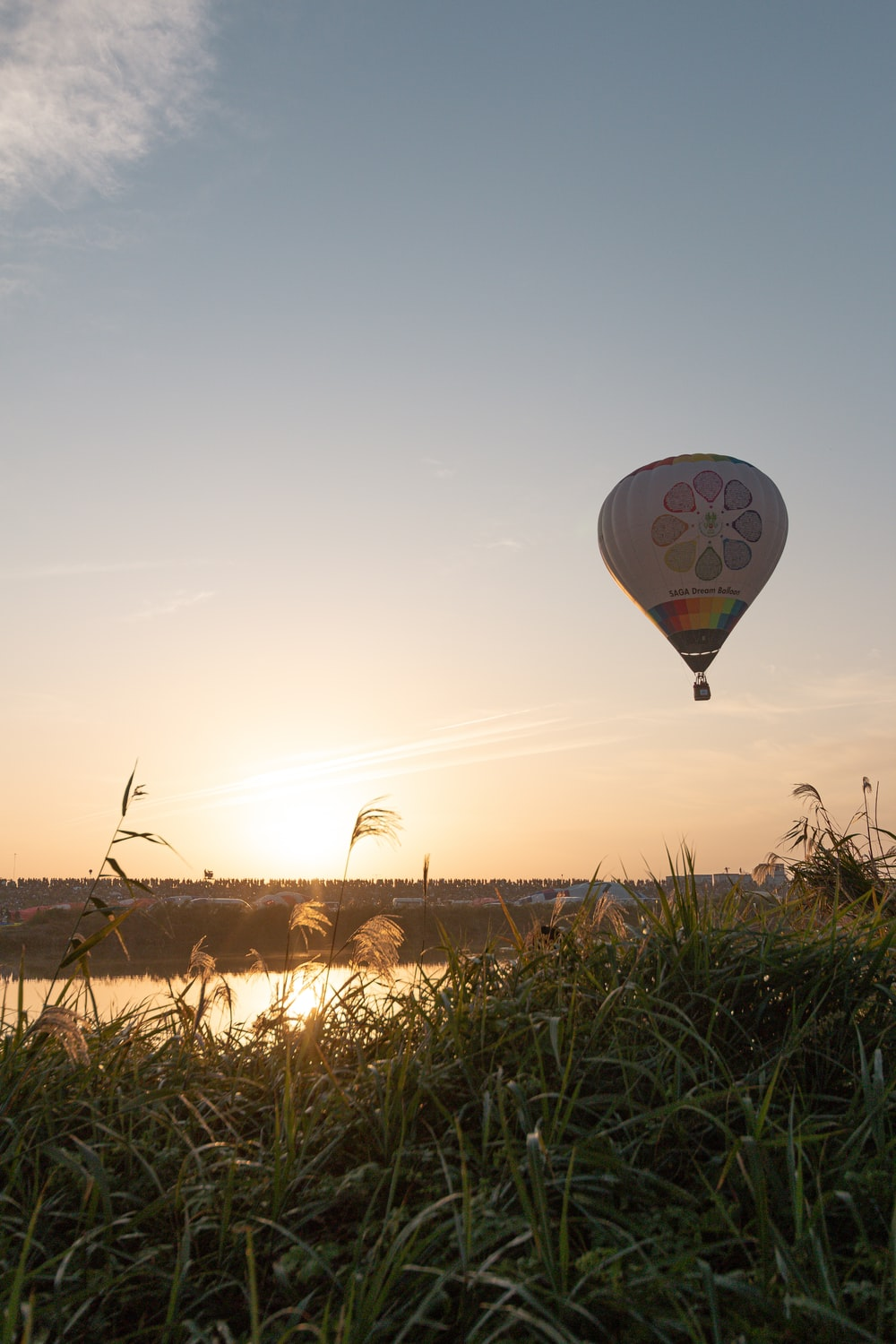 hot air balloon flying over the field during daytime