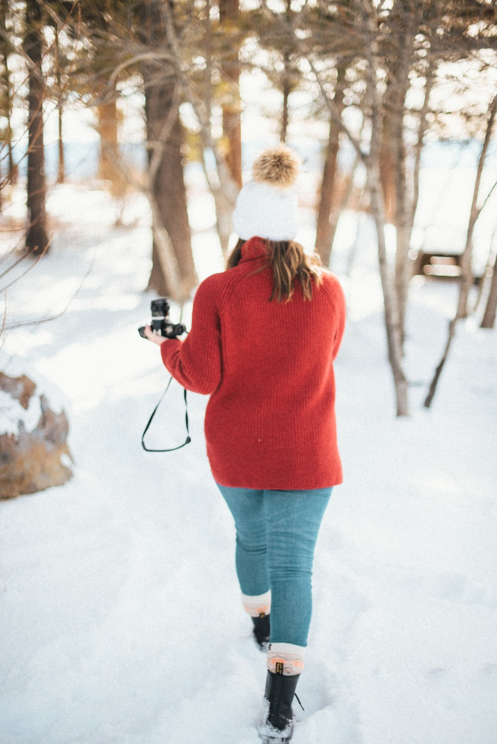 woman in red sweater and blue denim jeans holding camera on snow covered ground during daytime