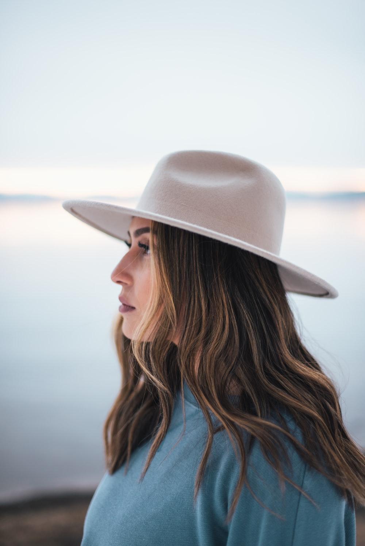 woman in blue shirt wearing white fedora hat