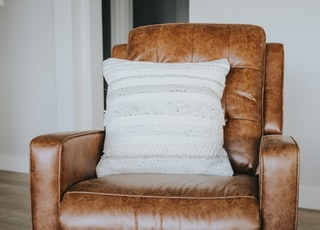brown leather armchair with white throw pillow