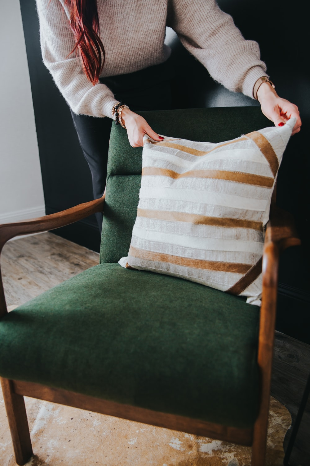 person holding white and brown striped throw pillow