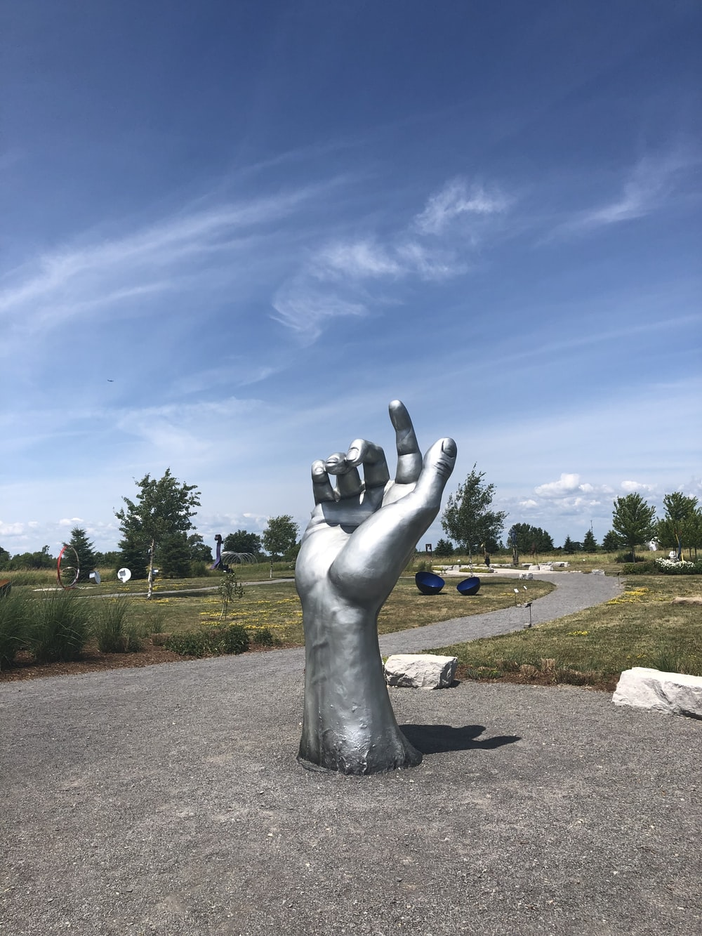 gray statue on brown soil under blue sky during daytime