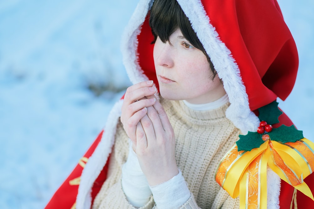 woman in white turtleneck sweater covering her face with red and white textile