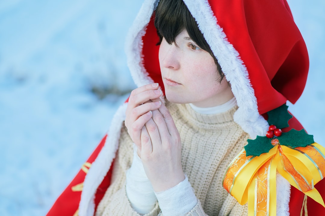 Beautiful young girl in a sweater and cape with a red hood. On her left shoulder she has a gold ribbon with oak leaves and red berries. A winter portrait photo of a cute lady. Face fantasy woman in red hood.