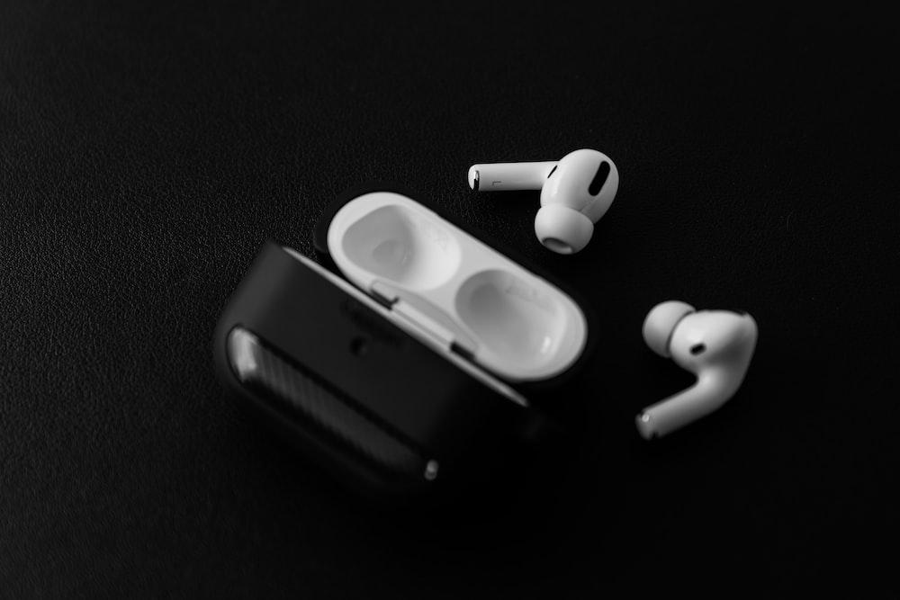 white apple earpods beside black leather case