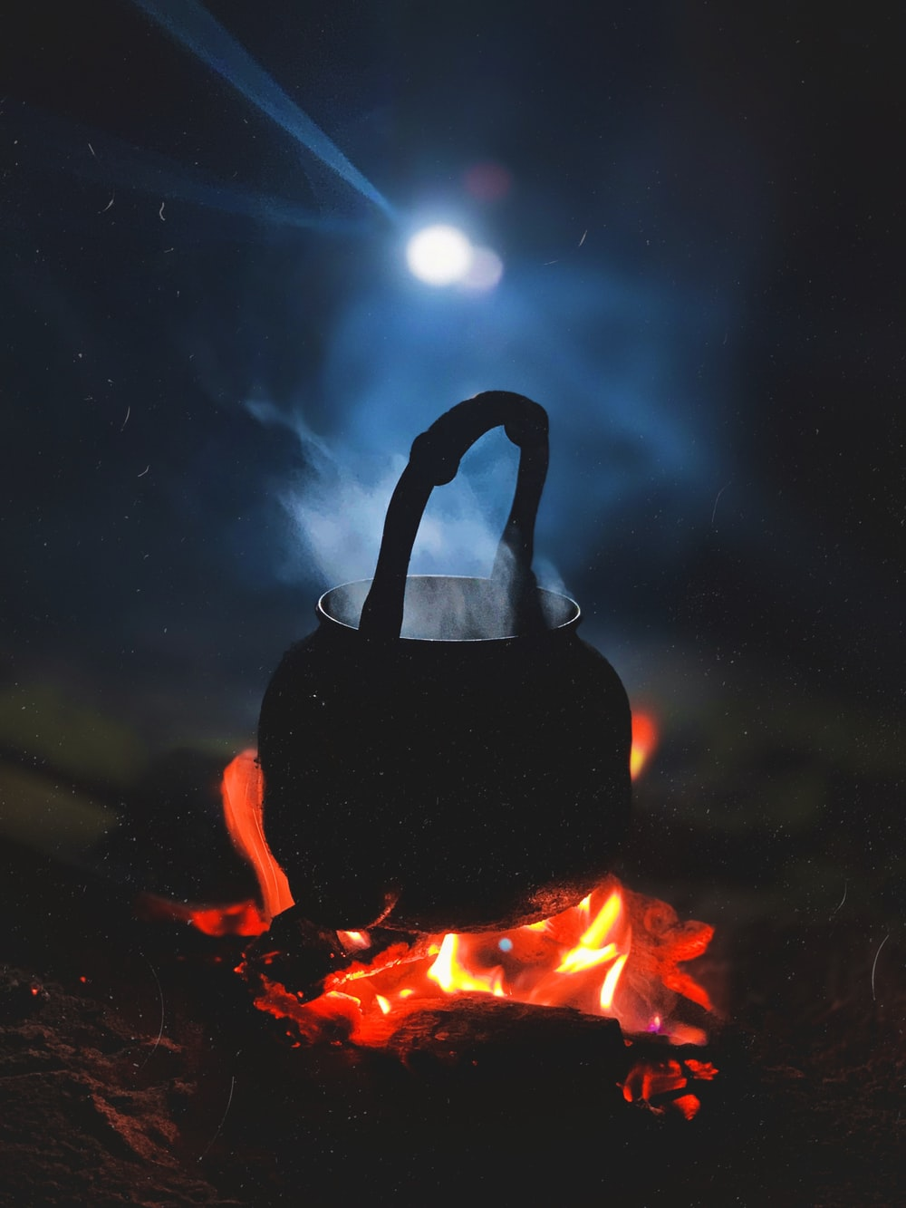 person in black hoodie standing on fire during nighttime