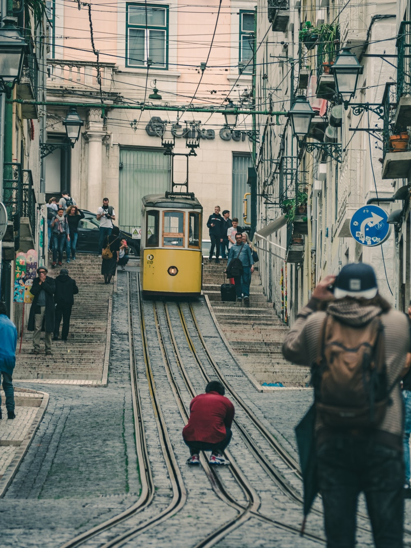 people walking on the street near yellow tram during daytime