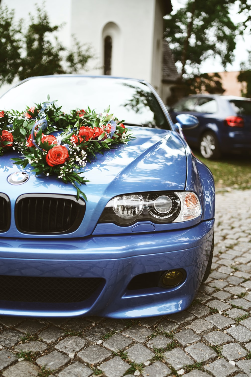 red and white roses bouquet on grey bmw car