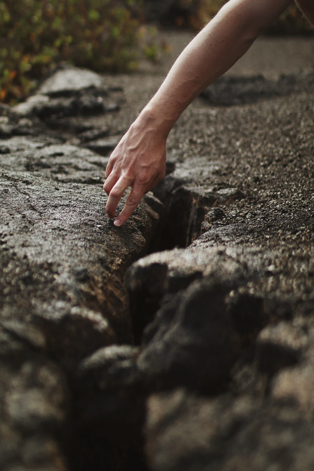 persons hand on gray rock