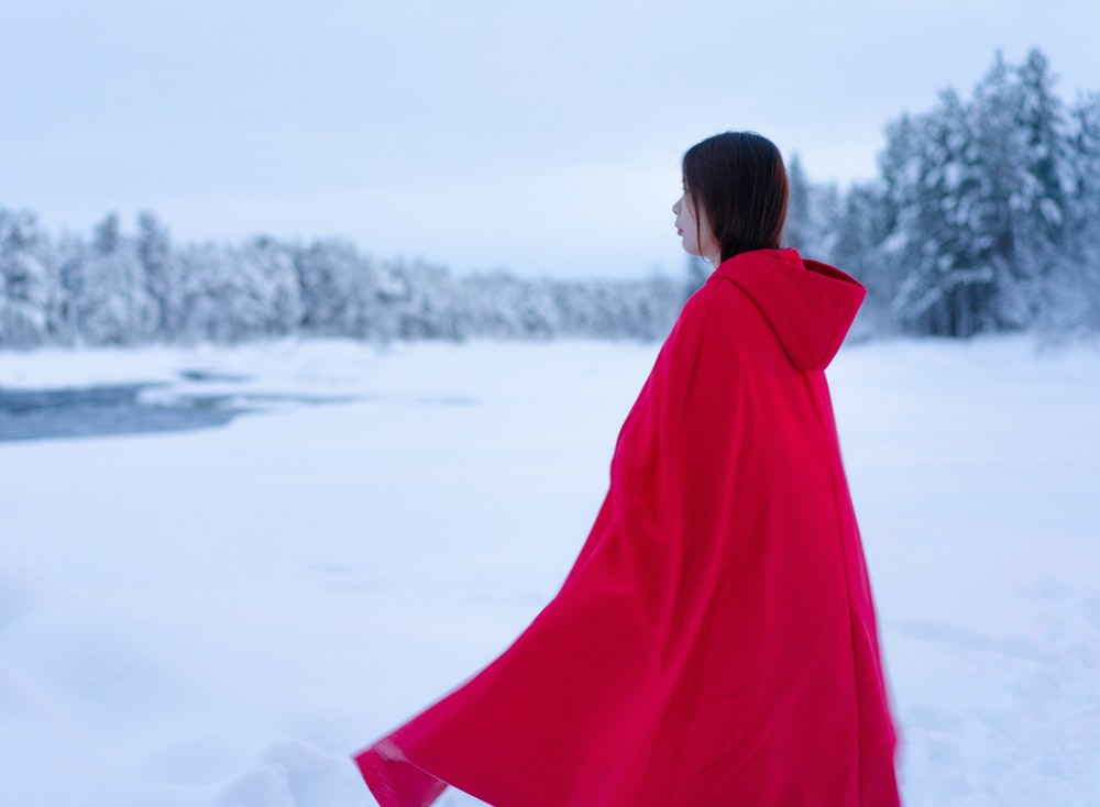 woman in red coat standing on snow covered ground during daytime