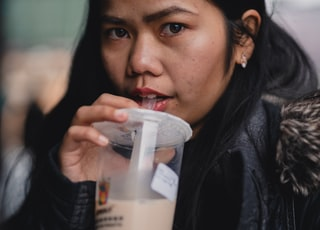 woman in black leather jacket holding white plastic cup