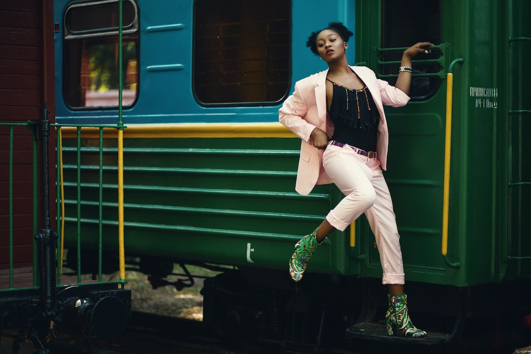 Woman In Black Tank Top and White Pants Standing Beside Green Train During Daytime - unsplash