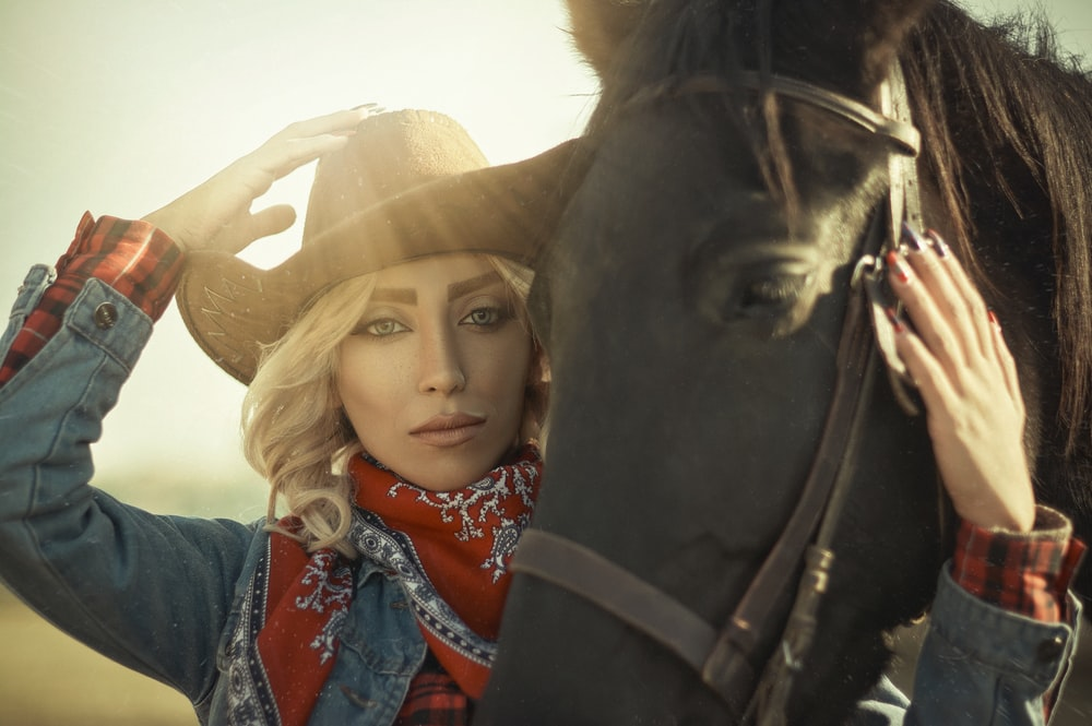 woman in blue denim jacket wearing brown cowboy hat beside black horse during daytime