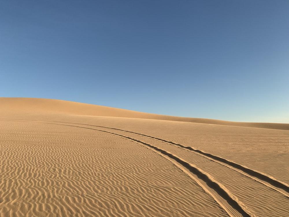 brown sand field under blue sky during daytime