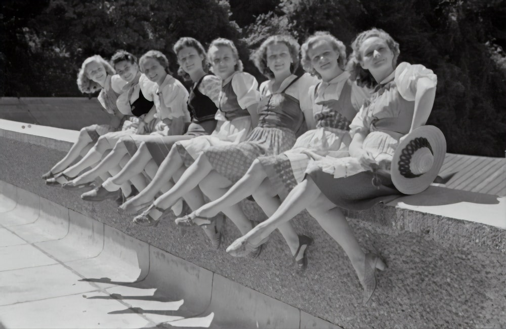 grayscale photo of group of women sitting on concrete bench