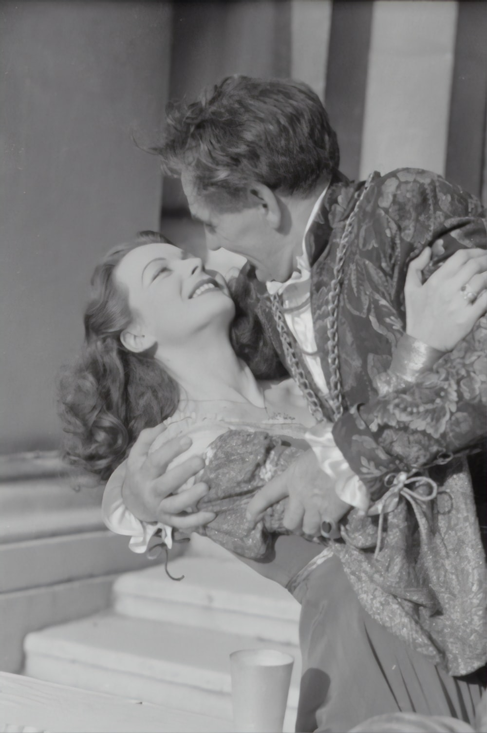 woman in white lace dress kissing mans cheek