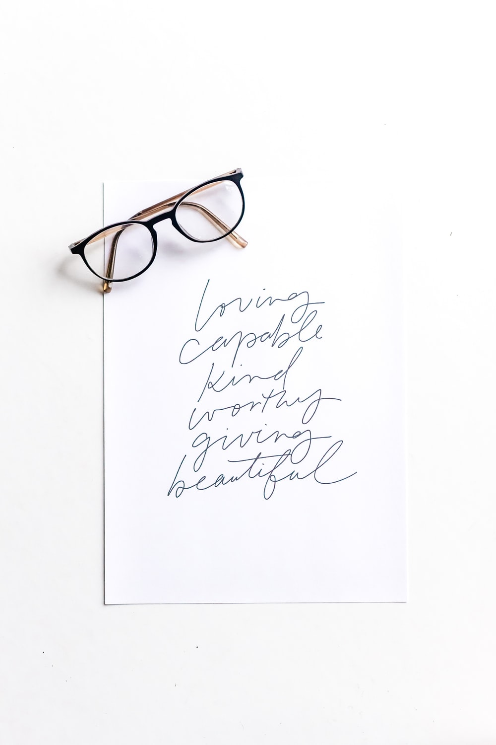 brown framed eyeglasses on white printer paper