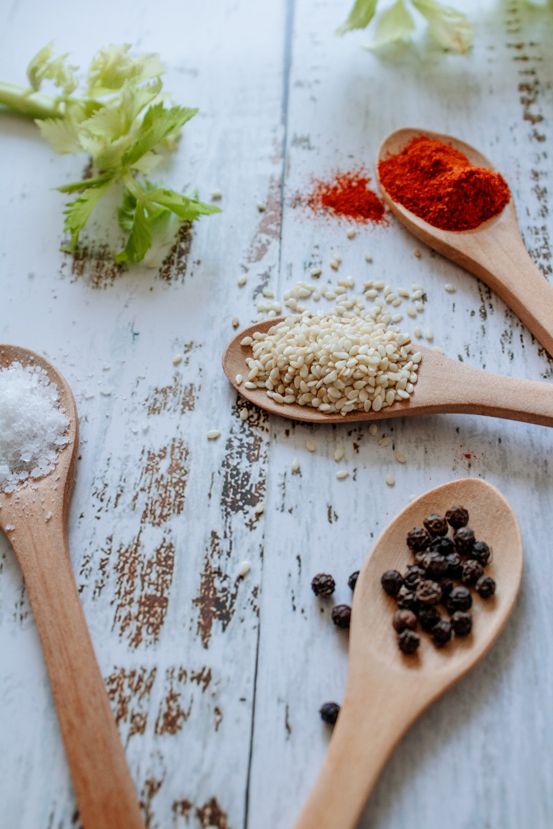 Spices and wooden spoons. Black pepper, sea salt, sesame seeds and red red pepper