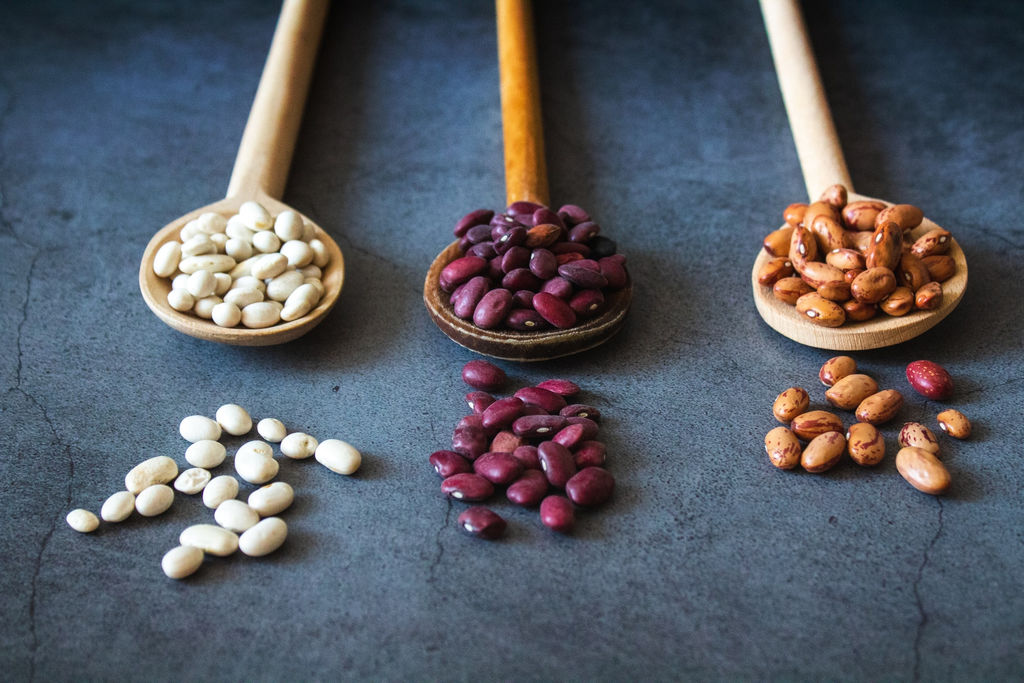 Different kinds of beans on dark background