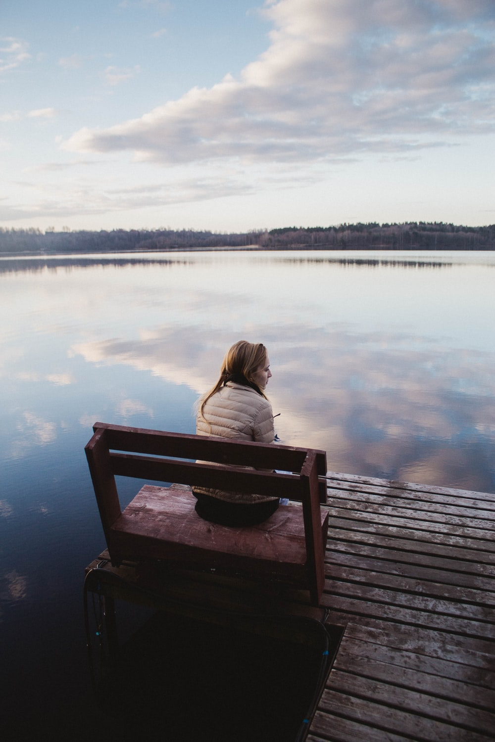 woman in gray hoodie sitting on brown wooden dock during daytime